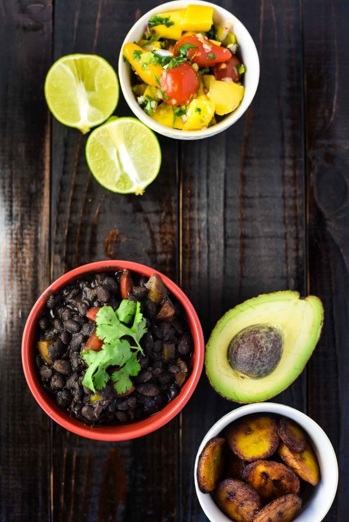 Ingredients for a vegan black bean bowl sit on a wooden tabletop. There are Cuban-style black beans, avocado, lime, fried plantains, and mango salsa.