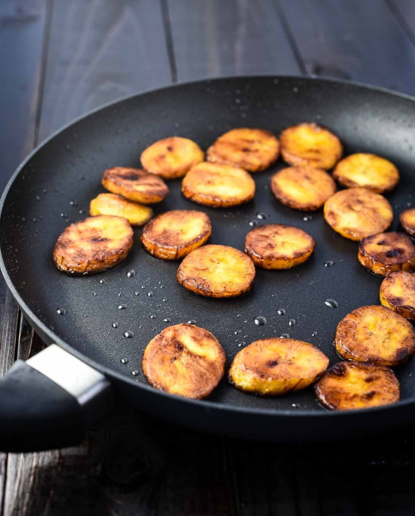 Fried plantains in a black skillet with oil. They are golden brown.