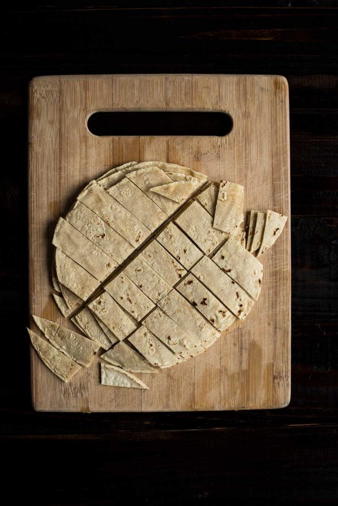 Corn tortillas sliced on a wooden cutting board. Ingredients for a vegan burrito bowl.