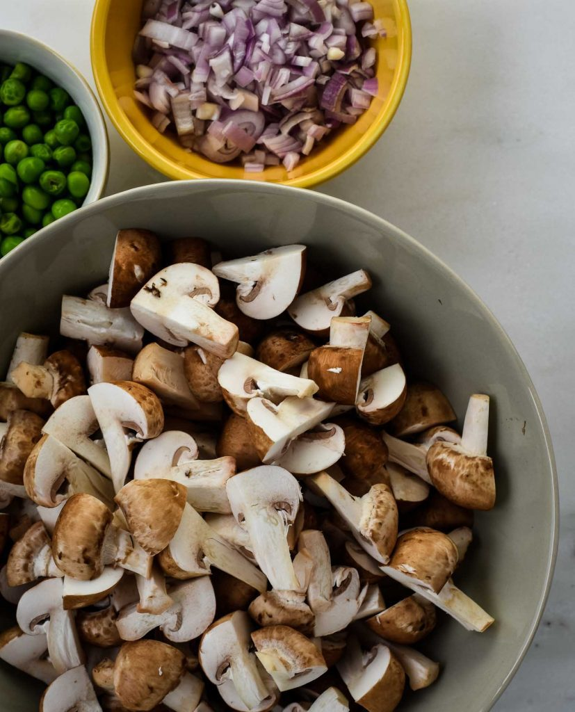 Vegan mushroom ingredients sliced and ready. Green peas in a white bowl, shallots in a yellow bowl, and sliced crimini mushrooms in a grey bowl.