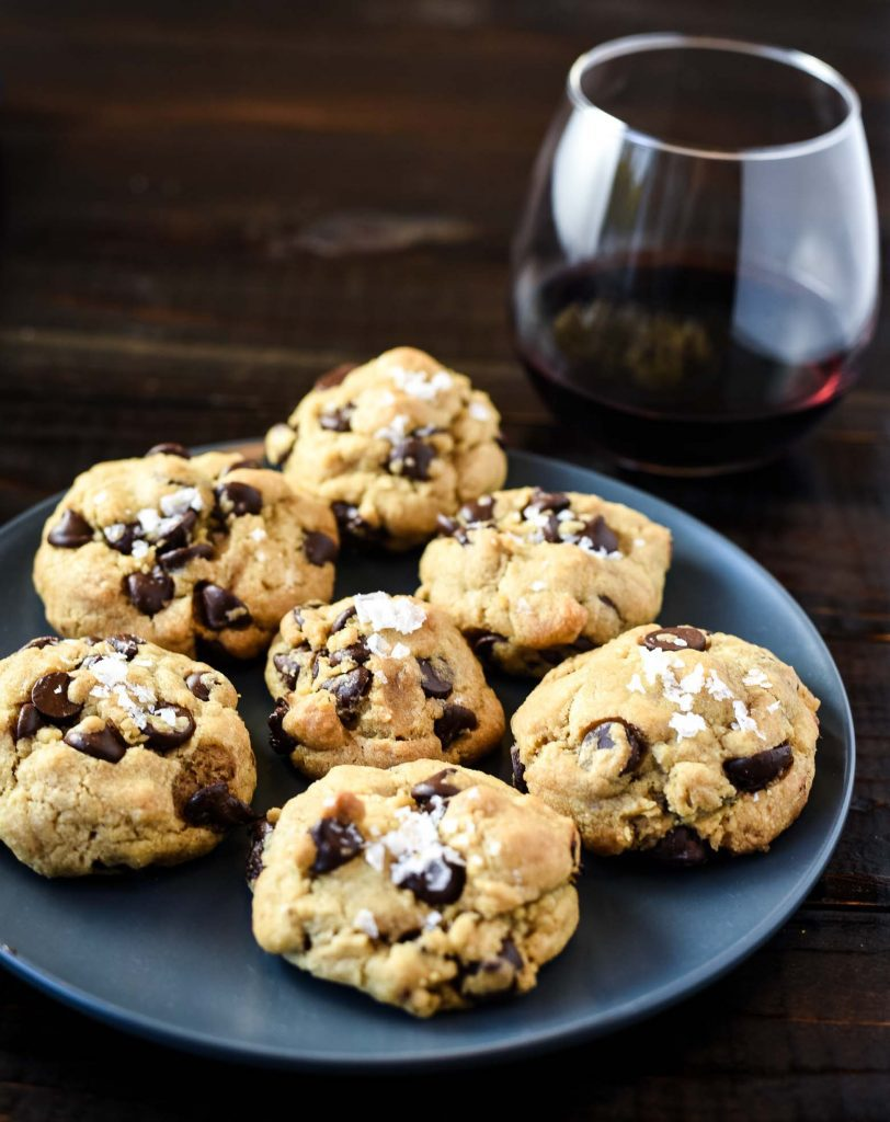 Vegan salted chocolate chip cookies sitting on a blue plate with a glass or red wine. The cookies are salted.