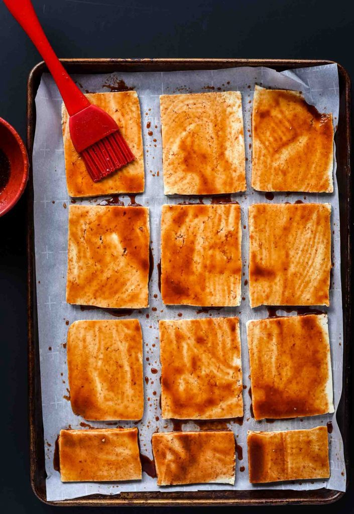 Sriracha Soy Baked Tofu getting marinaded before getting cooked in the oven. The tofu is on parchment paper on an old cooking sheet.