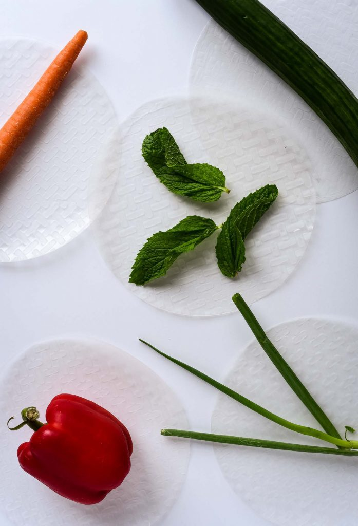 Fresh spring roll ingredients on rice paper wrappers on a white background. There is a red pepper, carrot, mint, green onion, and cucumber.