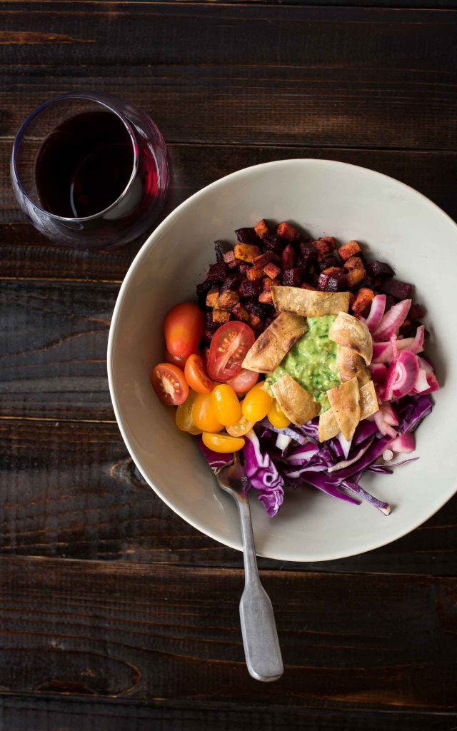 Vegan burrito bowl with glass of red wine on dark wood table. There is a grey bowl with rice, cumin spiced beets and sweet potatoes, guacamole, chopped cherry tomatoes, red cabbage, and quick pickled onions.
