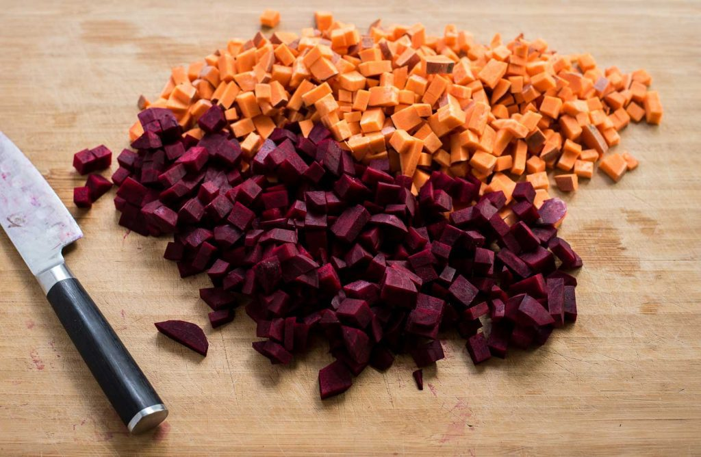 Finely chopped beets and sweet potatoes on a wooden cutting board with a knife. Ingredients for cumin-spiced vegetables in vegan burrito bowl recipe.
