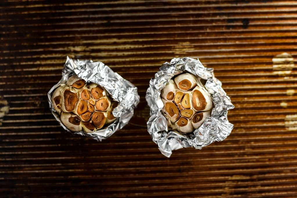 Two heads of roasted garlic in tinfoil on a distressed cooking sheet. These are ingredients for a vegan mac and cheese recipe.