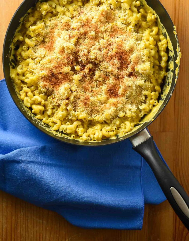 Vegan mac and cheese with green chiles in skillet. The dish has been broiled. There is a sky blue linen on the table. It looks very cheesy.