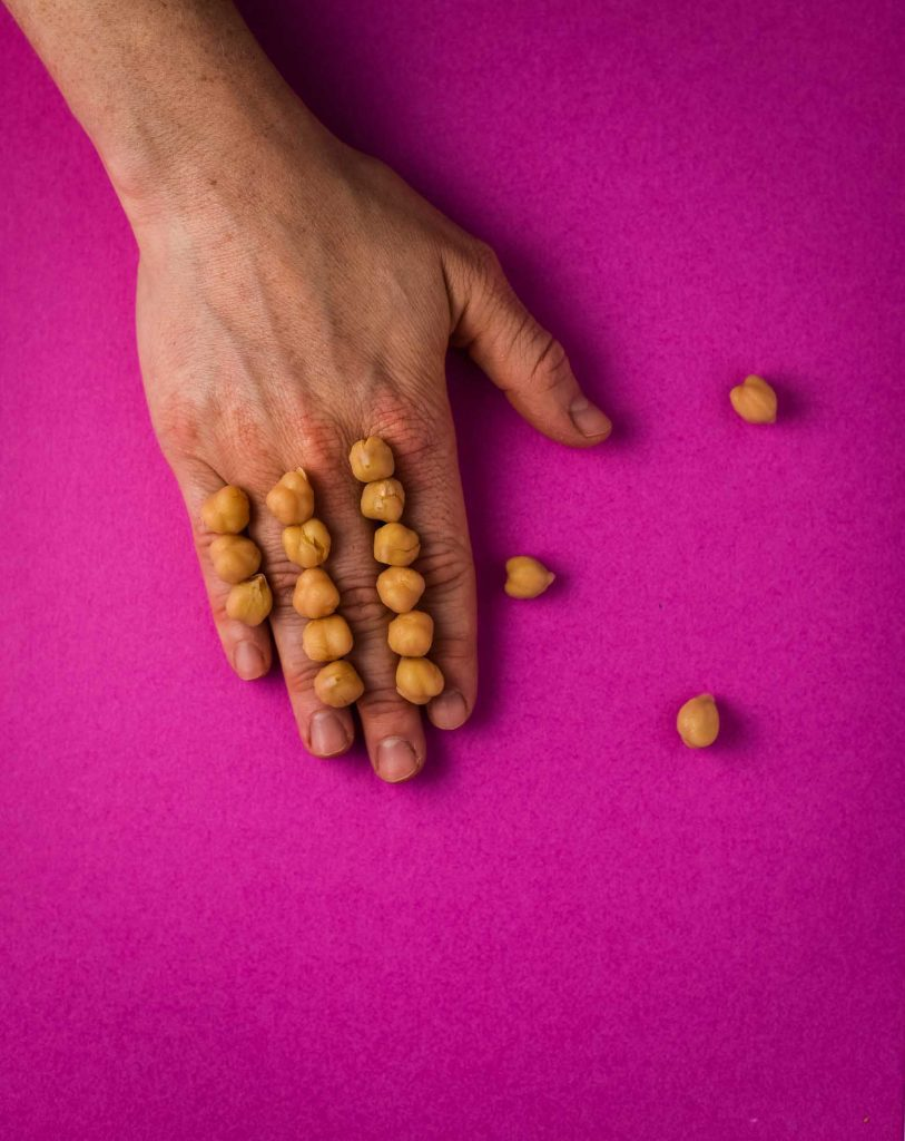Raw chickpeas stacked on hand on pink background. Three chickpeas have fallen off the hand. Recipe for Kale salad with roasted chickpeas.